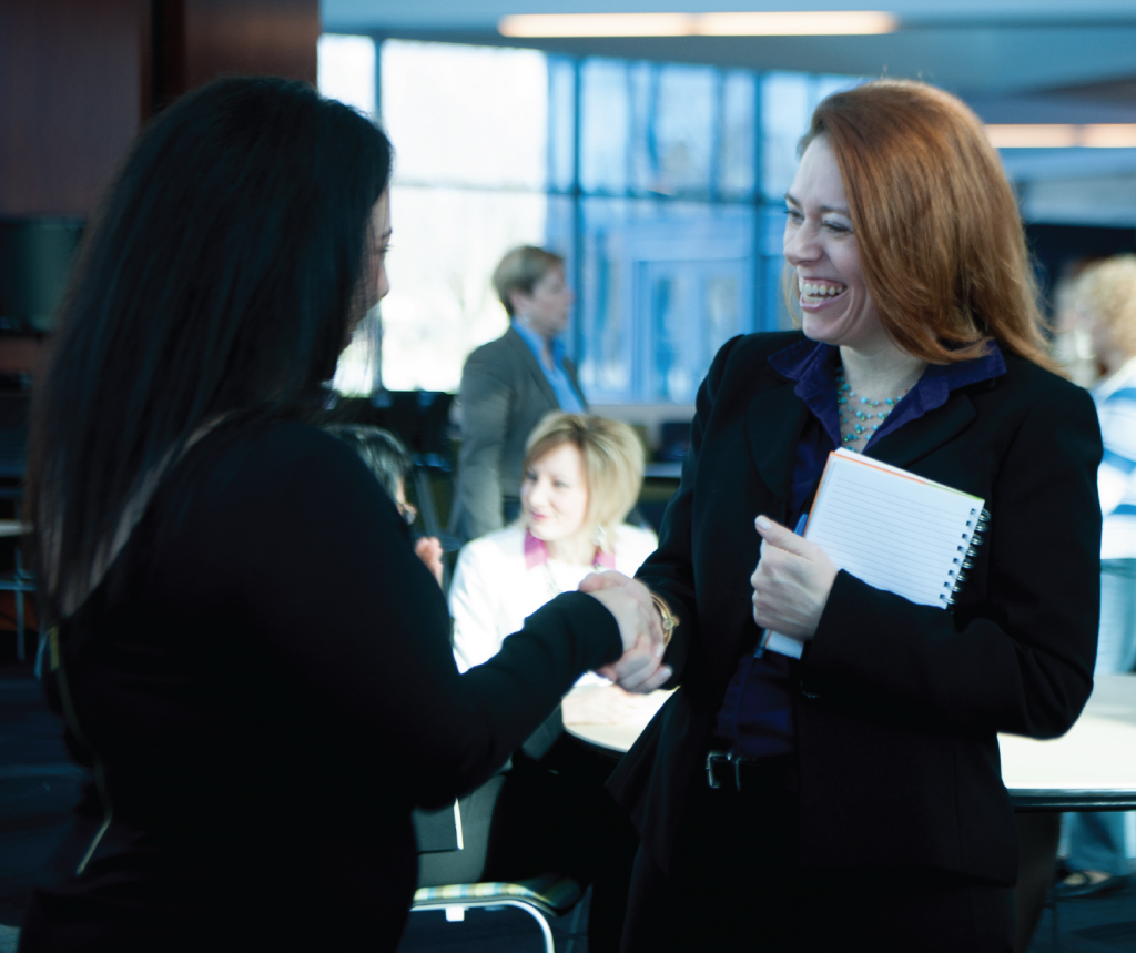 two women shaking hands at an event