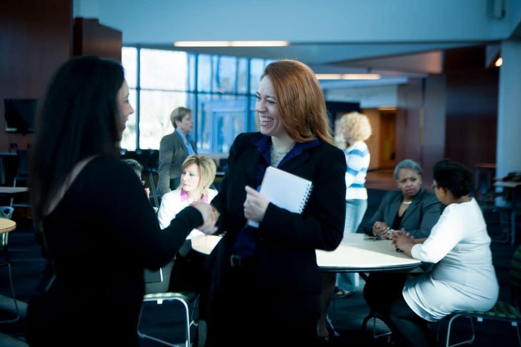 women shaking hands at an event